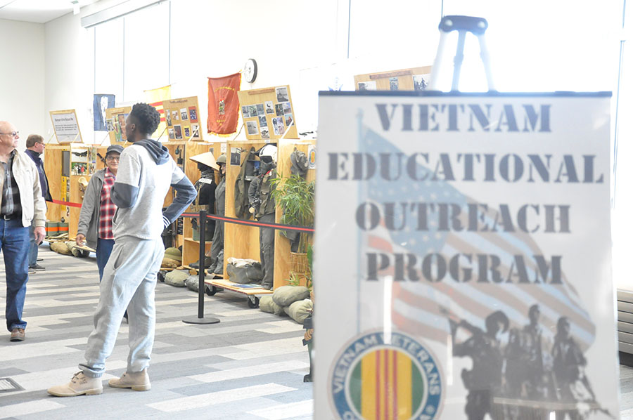 Students visit with Vietnam War veterans and look at the displays set up at the Truax campus on March 29