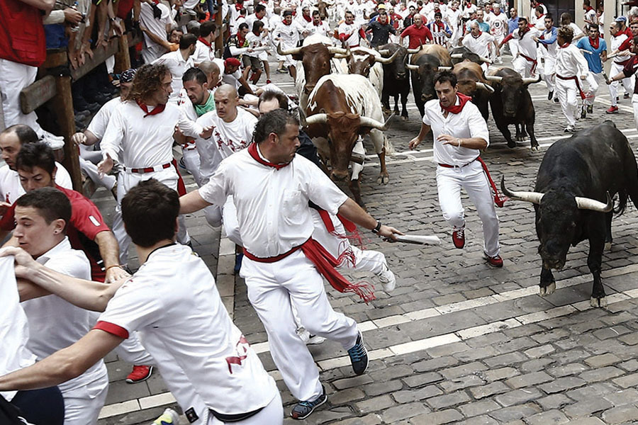 Several runners, or mozos, are chased by bulls, from El Tajo y la Reina ranch, on July 8, 2015, in Pamplona, northern Spain.