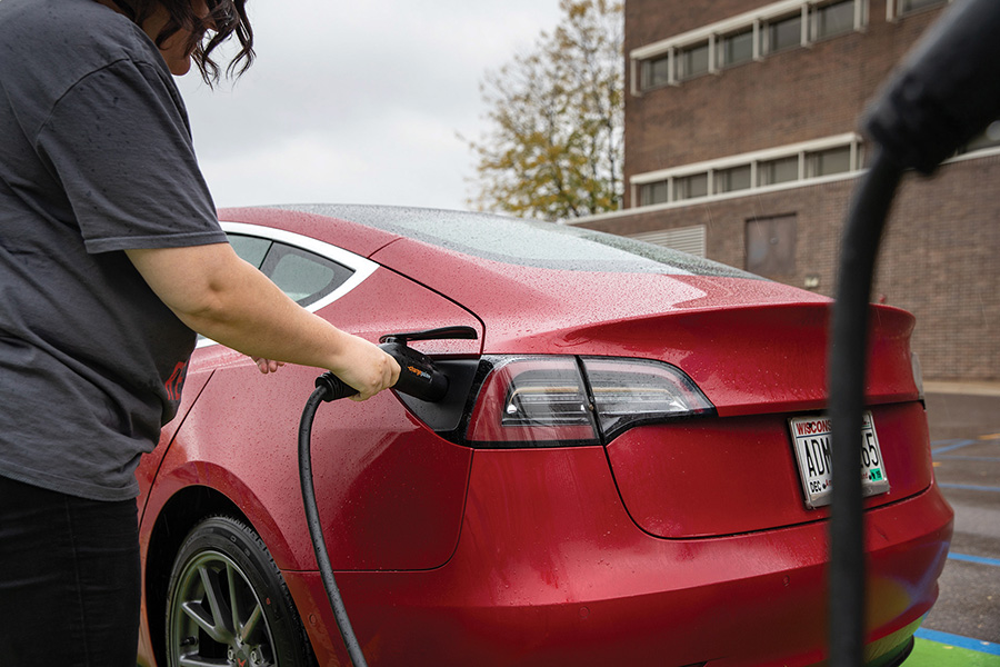 Madison College student Emily Dimond charges her car using one of the MGE charging stations at the college's Truax Campus.