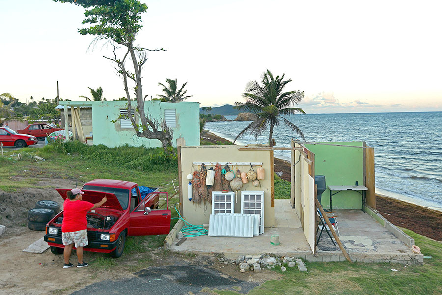 A year after the hurricane, Yamary Morales Torres was rebuilding her mother's home on the waterfront in Yabucoa. The house next door, foreground, which belonged to her brother, was left with only three walls standing.