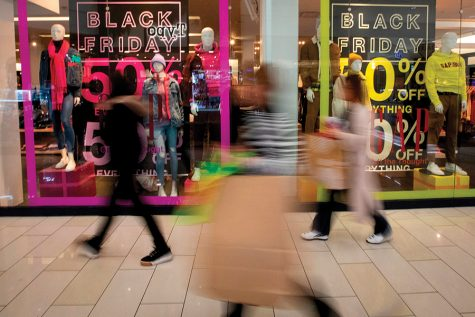 Shoppers walk past signs advertising Black Friday sales at the GAP. As enticing as sales are, remember to stay within your holiday budget, reminds marketing instructor Kristen Uttech.