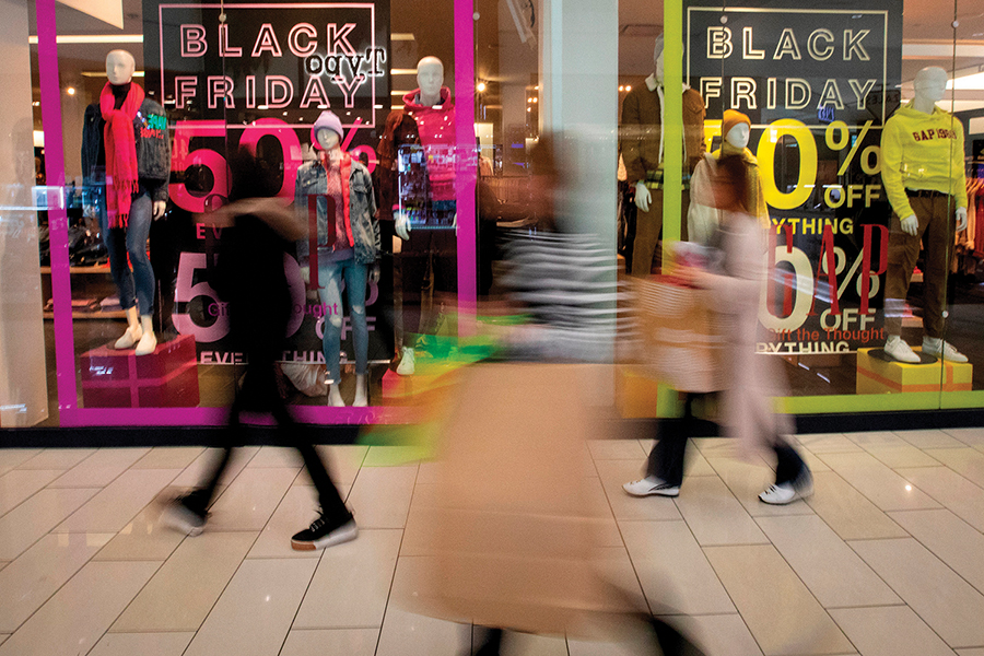 Shoppers+walk+past+signs+advertising+Black+Friday+sales+at+the+GAP.+As+enticing+as+sales+are%2C+remember+to+stay+within+your+holiday+budget%2C+reminds+marketing+instructor+Kristen+Uttech.