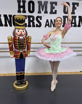 Sydney Bruce, a student at Madison College, poses in her costume next to a life size nutcracker.