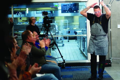 Chef Graham Elliot enthusiastically greets the crowd at the December Chef Series event at Madison College's Truax Campus.