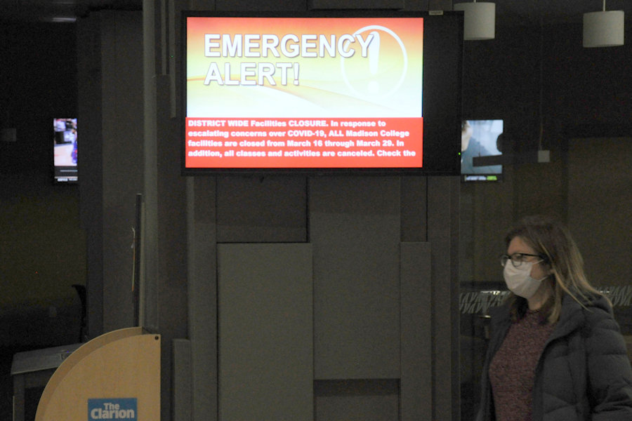 A WolfPack Alert notice on one of the campus monitors inside the Madison College main Truax building announces the initial campus closure, which has now been extended through May 15.
