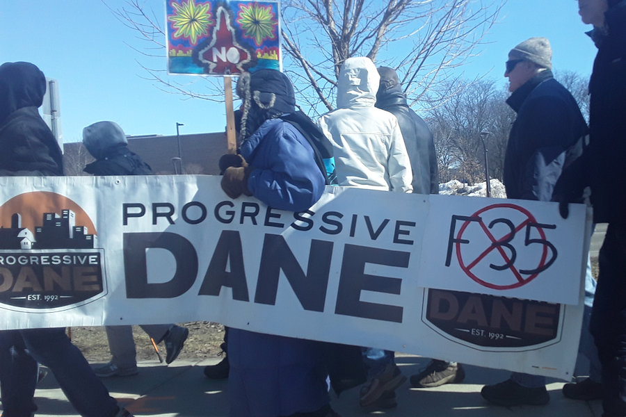 Protestors march past the Madison College Truax Campus on their way to the airport in opposition to plans to bring F-35 fighter jets to the Dane County Regional Airport.