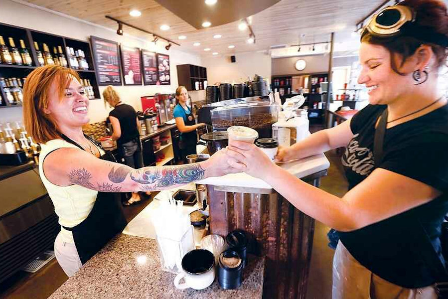 A barista with tattoos on her arms hands a coffee to a patron.