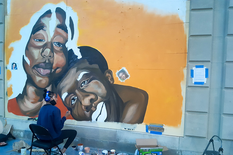 Artist Shiloah Symone Coley while working on the mural which now stands on N. Fairchild St at the side of the Overture Galleries building. Her art is inspired by Aiyana Mo'Nay Stanley and Cameron Tillman who as children were murdered by police forces and stories went untold.