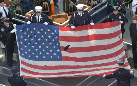 A U.S. flag recovered from the 9/11 attacks is displayed by New York City Police officers and firefighters during the ceremony marking the 10th anniversary of the terrorists attack in 2011.