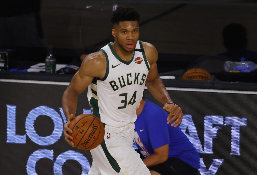 Giannis Antetokounmpo of the Milwaukee Bucks moves the ball up the court against the Orlando Magic on Aug. 22. The NBA will resume play in a little more than a month.