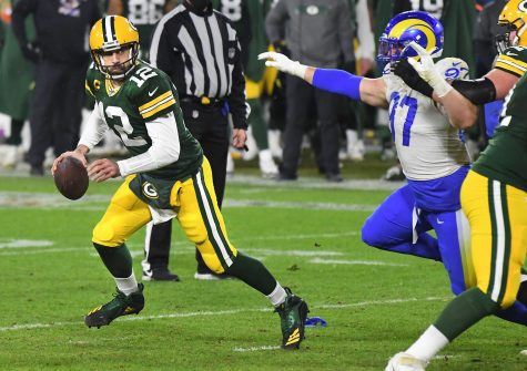 Green Bay Packers quarterback Aaron Rodgers (12) looks for a receiver as Los Angeles Rams defensive lineman Morgan Fox (97) pursues during an NFC Divisional playoff game at Lambeau Field in Green Bay on Jan. 16.