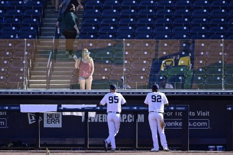 The New York Yankees' Chris Gittens (92) and Trey Amburgey (95) talk with a fan through plexiglass due to the COVID 19 pandemic after a spring training game against the Toronto Blue Jays in Tampa, Florida, on Feb. 28.