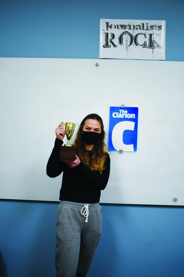 Editor-in-chief+Anica+Graney+holds+one+of+the+trophies+the+Clarion+received+in+a+past+contest.