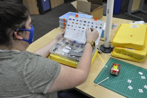 A student works to put together a STEM club kit.