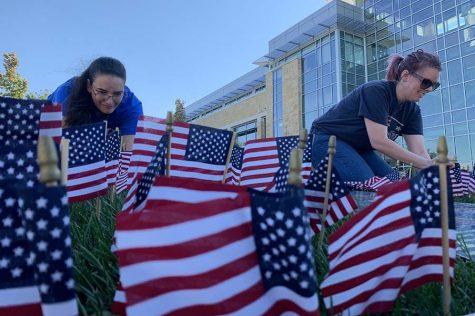 Phi Theta Kappa members set up a flag display on campus.
