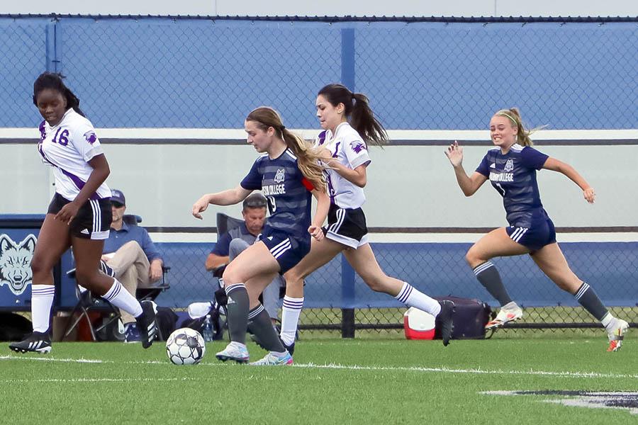 WolfPack womens soccer player Elizabeth Foye fights to get past defenders.